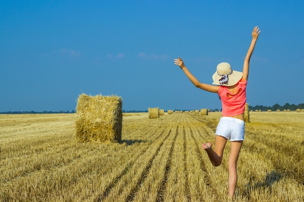 Beautiful happy young girl jumping for joy in the air near a haystack