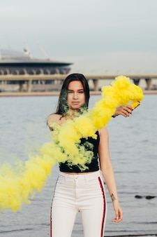 Beautiful happy young girl at the seaside hold a light up colored smoke bombs.