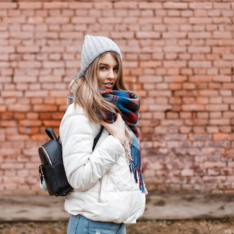 Beautiful happy young girl in a white jacket and bright scarf with a black bag near a brick wall