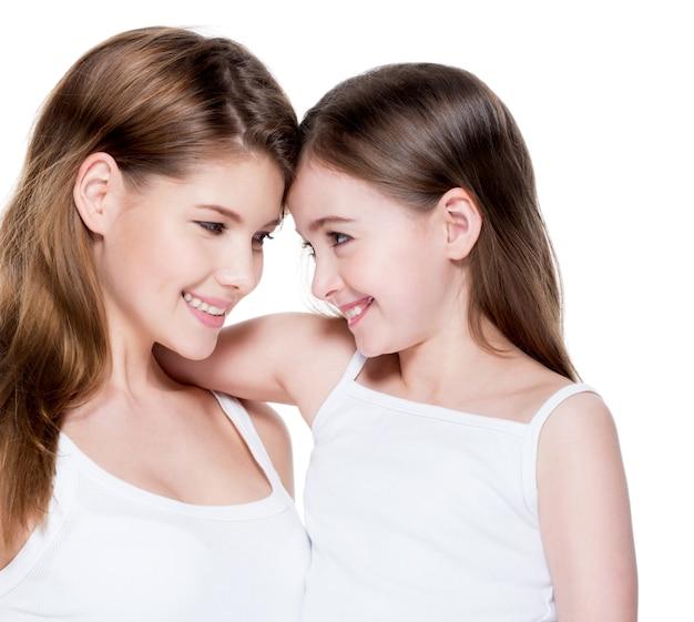 Bella e felice giovane madre con una piccola figlia di 8 anni si abbracciano in studio