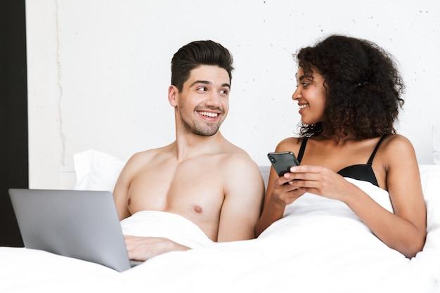 毛布の下のベッドでリラックスした美しい幸せな若い多民族のカップル、ラップトップコンピューターを使用して男性、携帯電話を保持している女性