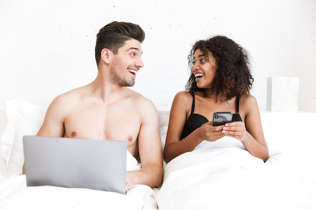 담요 아래 침대에서 편안한 아름 다운 행복 한 젊은 다민족 부부, 노트북 컴퓨터를 사용하는 사람, 휴대 전화를 들고 여자