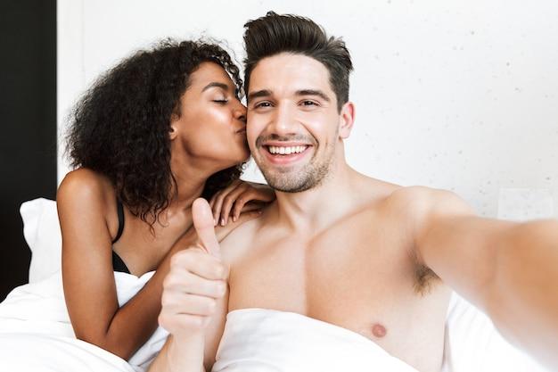 아름 다운 행복 한 젊은 다민족 부부, 담요 아래 침대에서 휴식, selfie를 복용