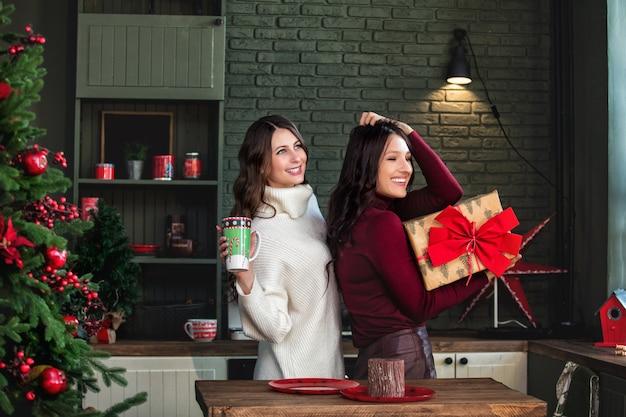 크리스마스 장식을 배경으로 부엌에 있는 아름다운 행복한 젊은 두 여성