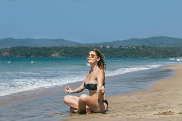 Beautiful happy young woman in bikini on sandy ocean beach