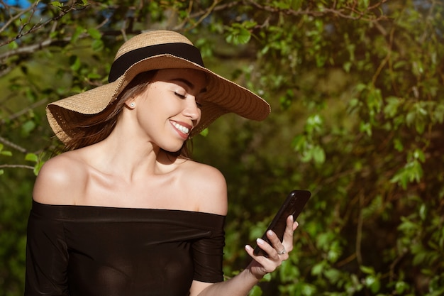 Beautiful happy young woman of caucasian ethnicity in a straw hat from the sun with large brim in a black dress with a phone in her hand smiling on a sunny summer day