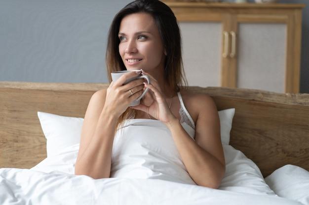 Красивая счастливая молодая женщина, выпивая чашку кофе или чая, лежа в постели после пробуждения утром. макрофотография портрет улыбающейся девушки, наслаждаясь ее напитком, расслабляясь у себя дома.