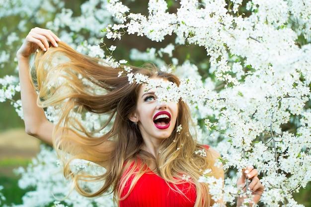 花の咲く春の庭で美しさを楽しんでいる美しい幸せな若い女性春の日に花で興奮した面白い女の子の表面