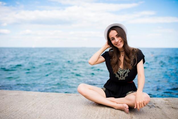 帽子をかぶった美しい幸せな若い女性が海岸で休んでいます