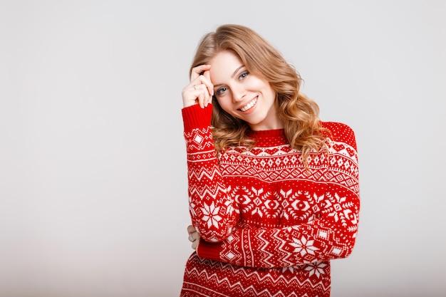 灰色の背景に赤い流行のセーターで美しい幸せな若い女性