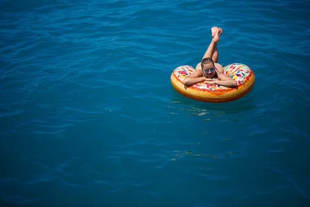 Красивая счастливая молодая женщина в купальнике с надувным кольцом, расслабляющимся в синем море. солнечный день, отдых на море, туризм
