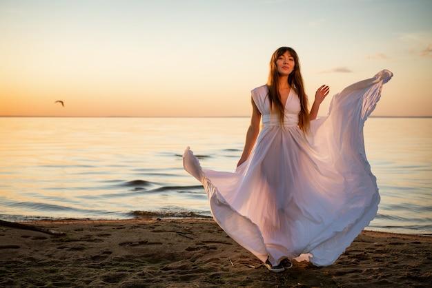 サンセットスタンドの海岸で白いロングドレスの美しい幸せな若い女性