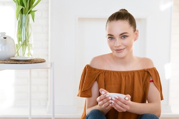 캐주얼 옷에 아름 다운 행복 한 젊은 여자는 꽃의 꽃다발과 함께 테이블 옆에 그녀의 손에 낯 짝과 함께 바닥에 장식 벽난로와 밝은 방에 앉아