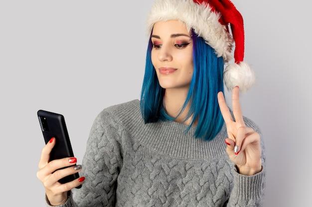 Красивая счастливая молодая женщина в шляпе санта делает селфи. рождество, новый год, концепция празднования