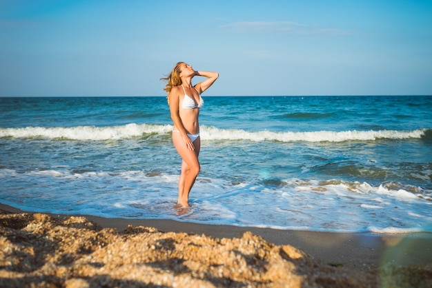 아름 다운 행복 한 젊은 여자는 휴가 동안 뜨거운 여름 날에 튀는 파도 옆에 젖은 모래에 서 있습니다