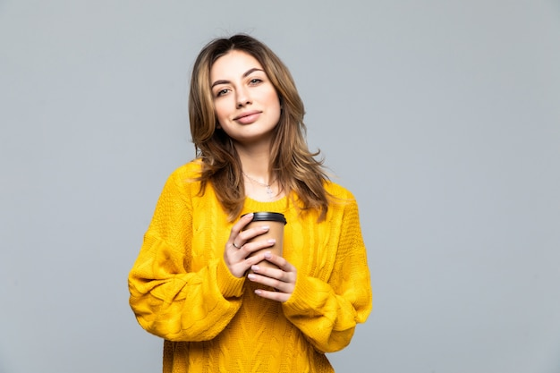 Beautiful happy young woman isolated over grey wall drinking coffee.