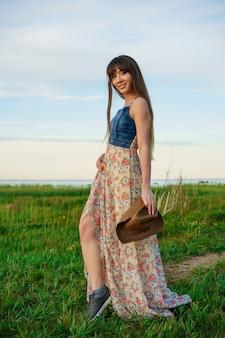 自然の上のドレスと帽子をかぶってゆるい美しい幸せな若い女性