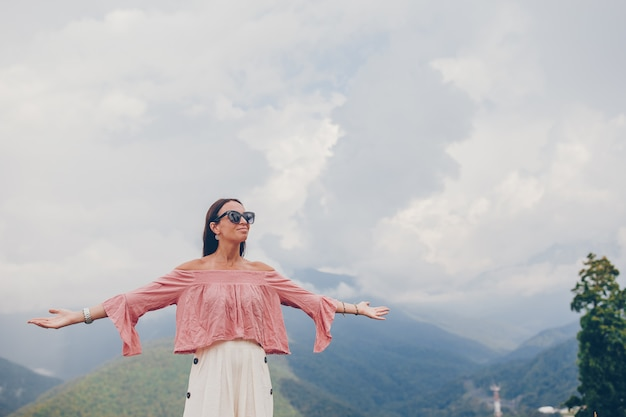 Beautiful happy young woman in mountains in the background of fog