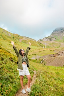 Beautiful happy young woman in mountains in the of fog