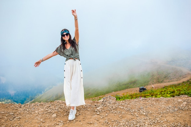 Beautiful happy young woman in mountains