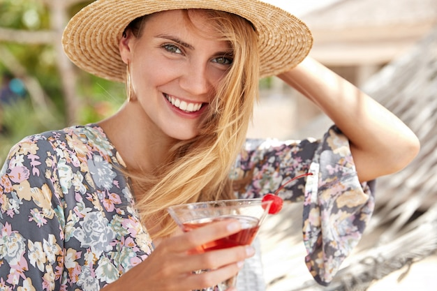 Beautiful happy young woman in summer style, has appealing appearance, smiles broadly, drinks fresh red cherry coctail, enjoys recreation after hard work, has trip abroad in hot exotic place