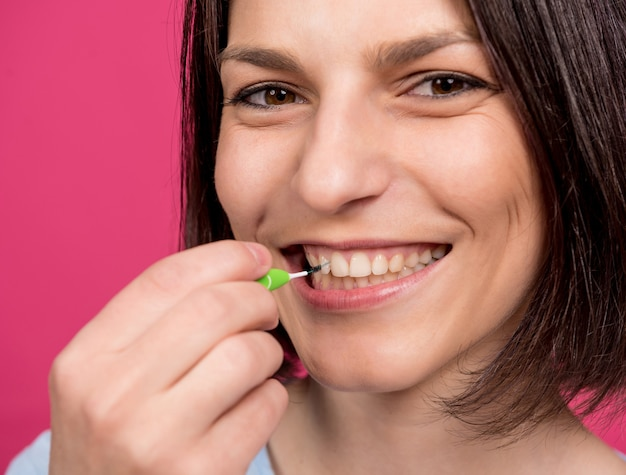 Beautiful happy young woman using interdental brush on the pink background