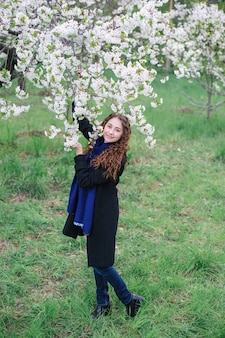 Beautiful happy young woman walking in a blossoming spring garden