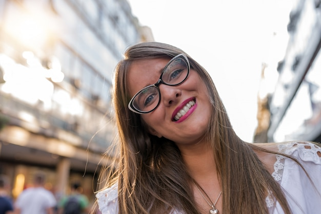 Beautiful happy young woman walking in the city