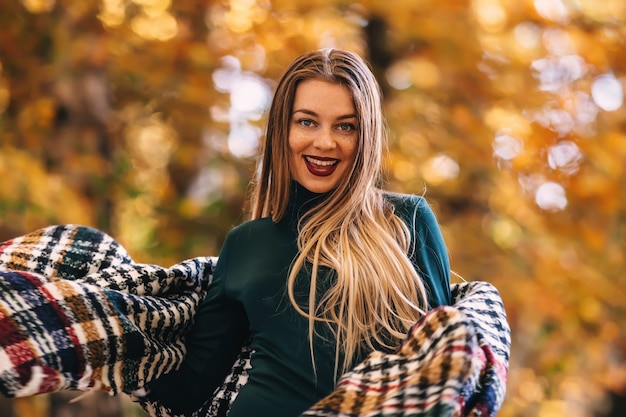 秋の公園を歩く美しい幸せな若い女性