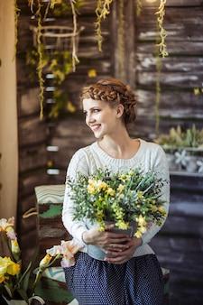 꽃의 부케와 함께 아름 다운 행복 한 젊은 여자