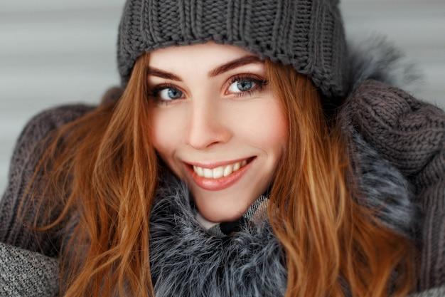 겨울 니트 모자와 장갑 빈티지에 미소로 아름 다운 행복 한 젊은 여자