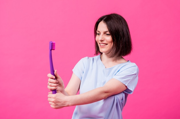 Beautiful happy young woman with big toothbrush on blank pink background