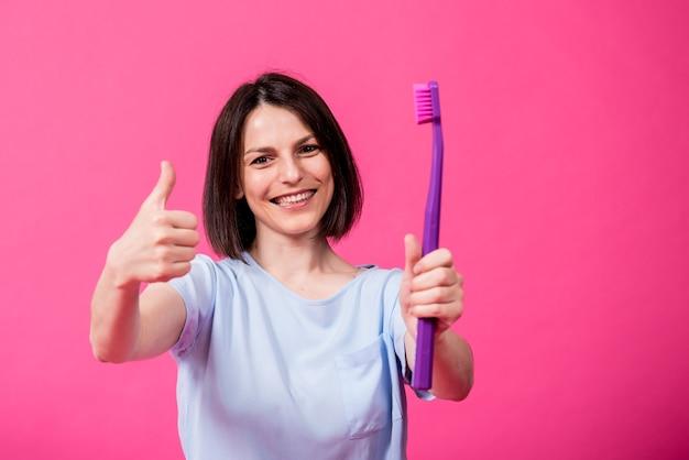 빈 분홍색 배경에 큰 칫솔을 가진 아름다운 행복한 젊은 여성