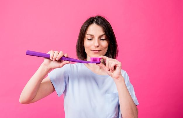 空白のピンクの背景に大きな歯ブラシを持つ美しい幸せな若い女性