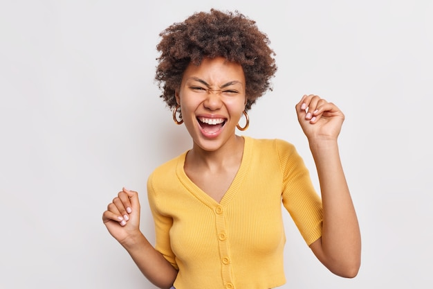 Beautiful happy young woman with curly hiar feels free and pleased raises hands up has fun dances joyful against white wall