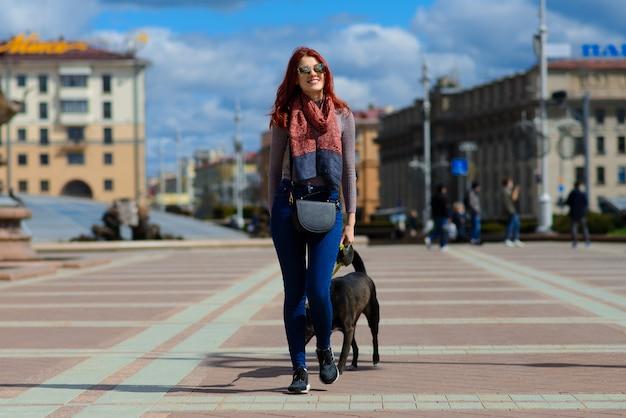 かわいい黒犬と美しい幸せな若い女性は、通りで楽しい時を過します。動物と人との友情の概念。