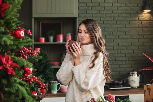 크리스마스 장식으로 부엌에서 얼굴에 미소를 띠고 있는 아름다운 행복한 젊은 여성