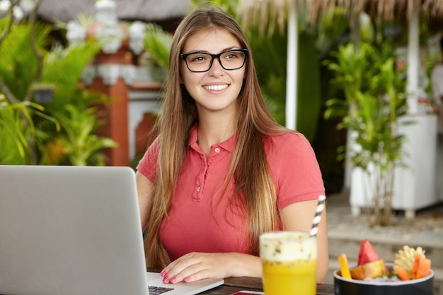 Beautiful happy young woman writer wearing stylish glasses typing on keyboard of her modern laptop pc