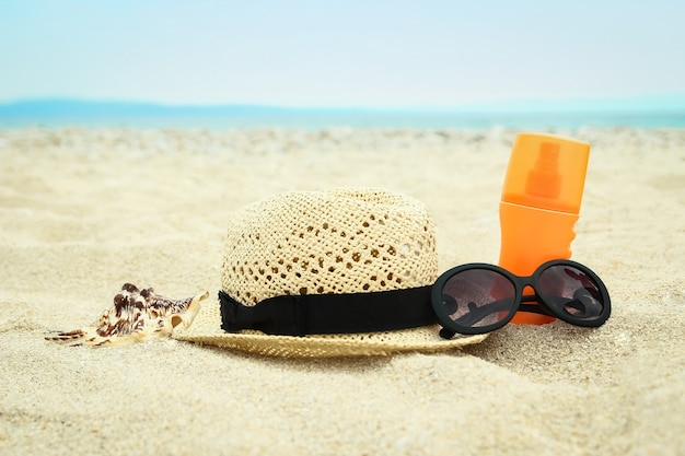 Beautiful hat with glasses and cream on the sea in the sand