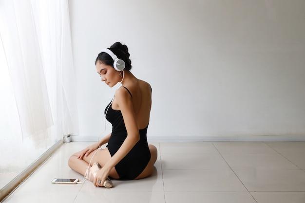 Красивая здоровая и спортивная азиатская молодая женщина в черной спортивной одежде с наушниками, практикующих балет с мобильного телефона