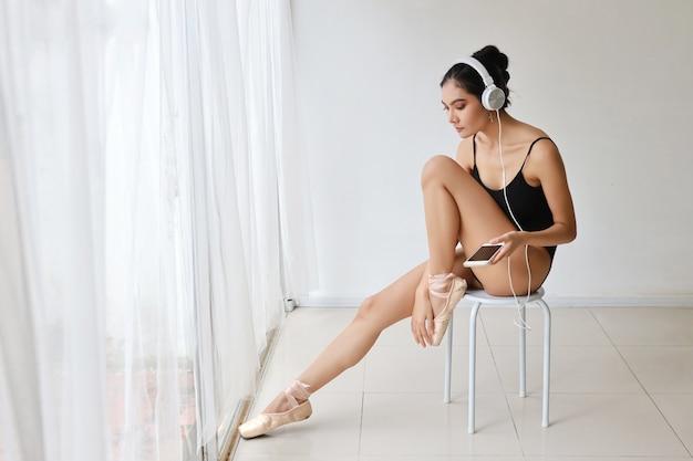 Красивая здоровая и спортивная азиатская молодая женщина в черной спортивной одежде с наушниками, используя мобильный телефон во время практики балета