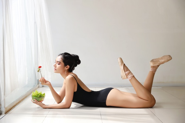 Beautiful healthy asian young woman eating salad after training ballet while lying down