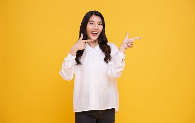 Красивая здоровая азиатская молодая женщина улыбается с его пальцем, указывая и глядя на светло-желтом фоне.