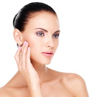 Красивое здоровое лицо молодой довольно белой женщины со свежей кожей, касающейся щеки рукой - изолированные на белом