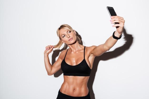 Bella sportiva in buona salute che prende un selfie mentre stando