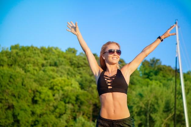美しい健康的なフィットの女性は、自然を気軽に楽しんで、笑顔で。屋外でのトレーニング、フィットネス、アクティブなライフスタイルのコンセプト