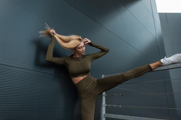 スニーカーで緑のトレーニング服を着たスポーティな体を持つ美しい健康的なフィットネスブロンドの女性は、街のモダンな金属製の建物の近くで足を伸ばして運動します