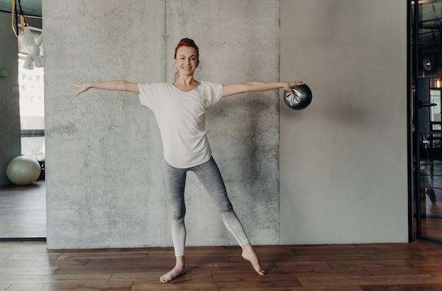 운동복을 입은 피트니스 클럽이나 스튜디오에서 손을 들고 두 번째 위치에 서서 작은 핏볼로 바레 운동을 하는 아름다운 건강한 생강 여성. 스포츠와 필라테스 개념