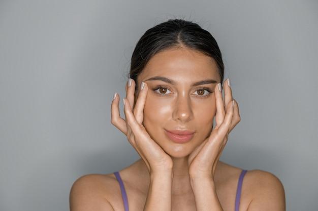 Красивая здоровая улыбающаяся кавказская женщина делает косметические процедуры в спа-салоне и салоне здравоохранения