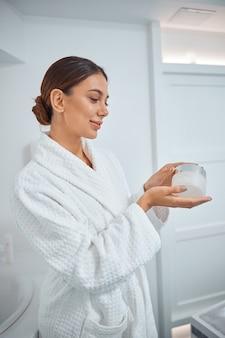 Красивая здоровая улыбающаяся кавказская женщина заботится о своей коже в ванной комнате